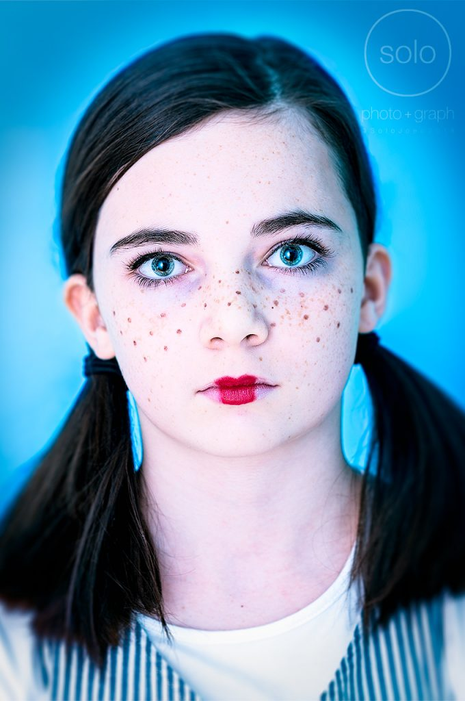 Photo of a young girl dressed up for Halloween with pig tails and freckles