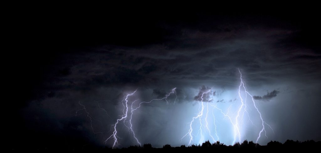 Nature photography photo of lighting striking the Earth on a dark stormy day