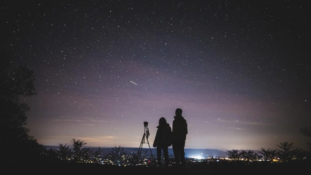 Astrophotography image of two photographers looking up at the stars with their camera on a tripod