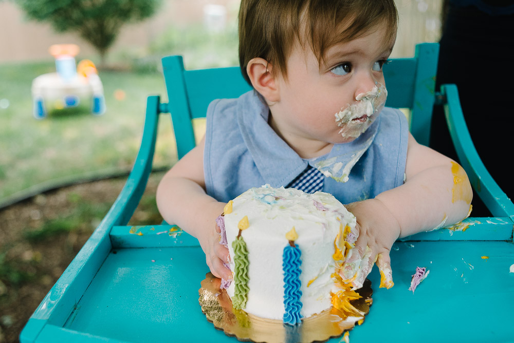 Image of a one year old eating cake on his first birthday shot on a 35mm lens