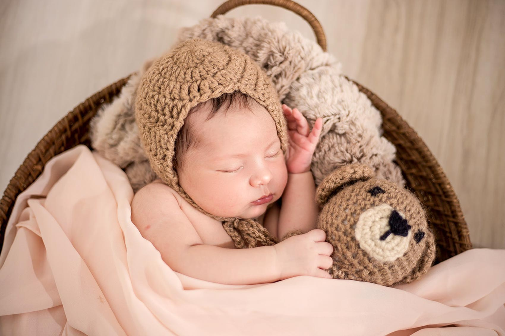 Image of a newborn baby with a hat on sleeping in a basket with a stuffed animal bear