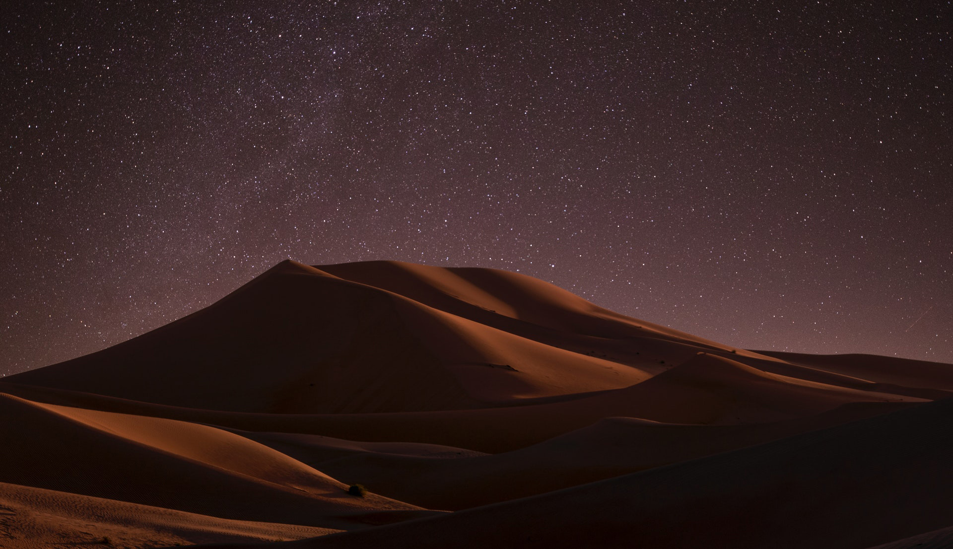 Image of a sand dune in a desert with a night sky and stars in the background