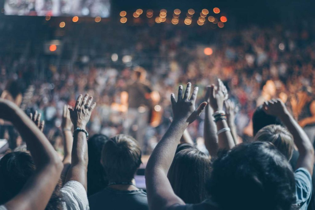 Image of people holding their hands up at a concert