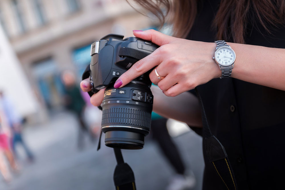 Image of a person holding a DSLR camera on a street