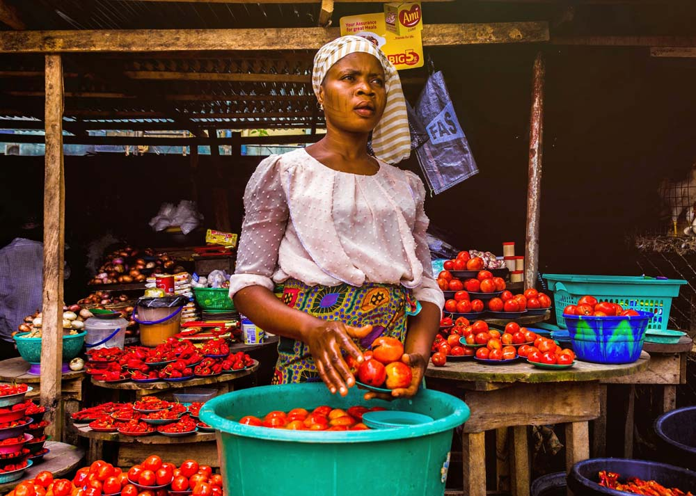 Documentary photo of a woman selling vegetables at a market