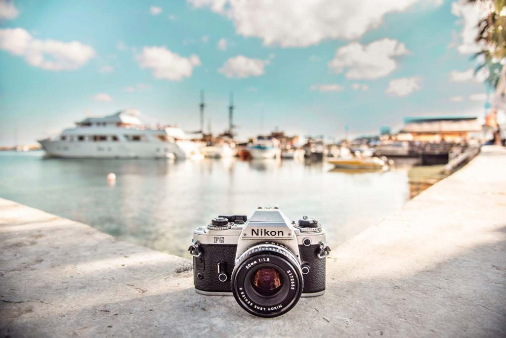 Image of a camera on a ledge in front of a bay with boats and a blue sky with some white clouds