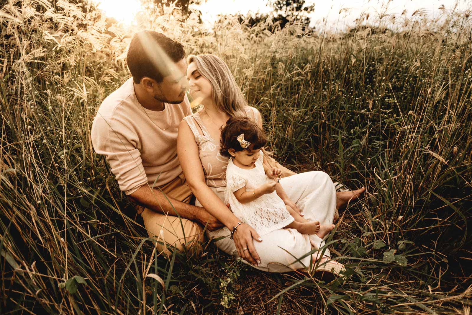 Family photo of a husband and wife with their baby in a field