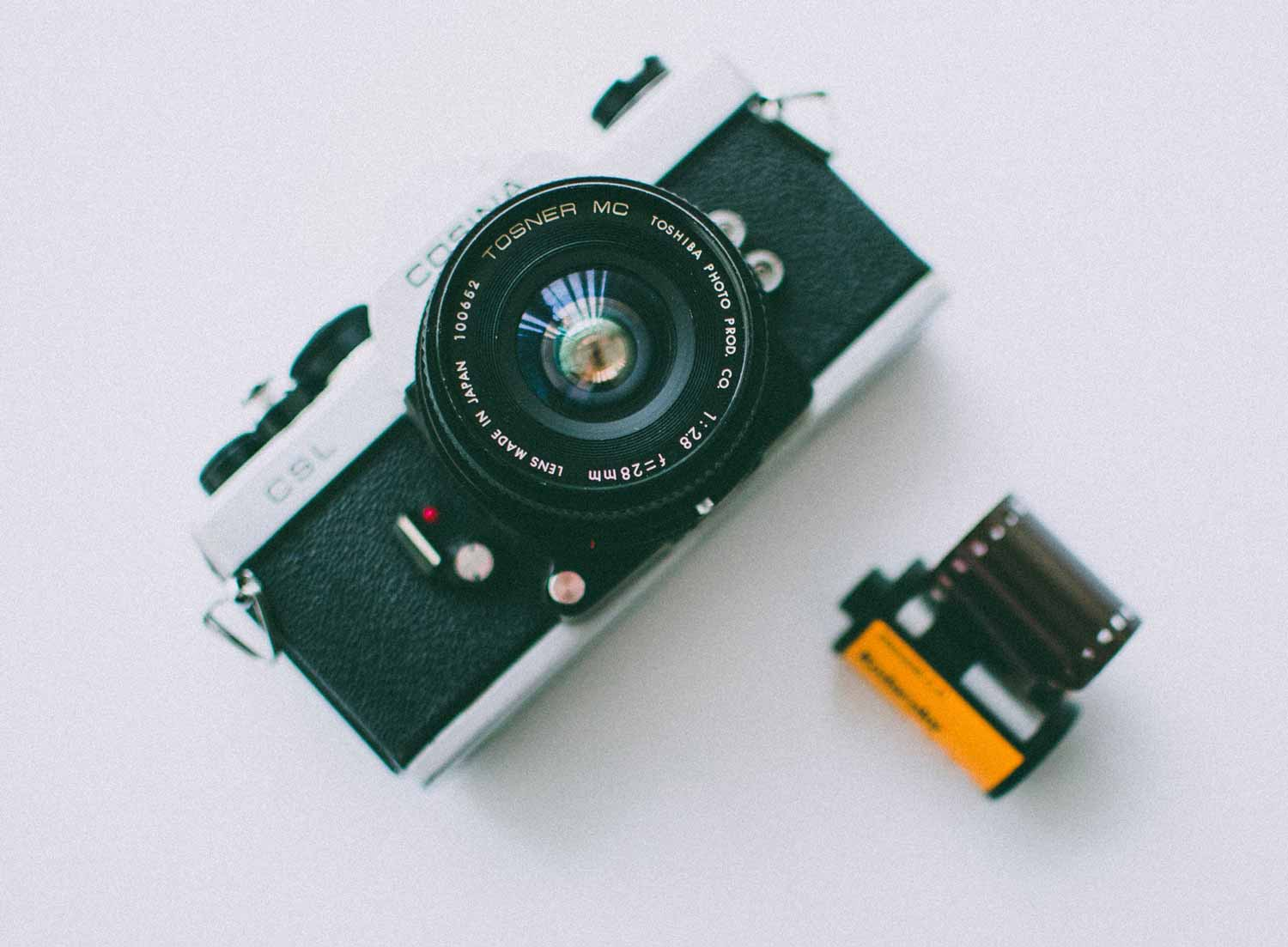 Image of a silver film camera and a film canister on a white surface