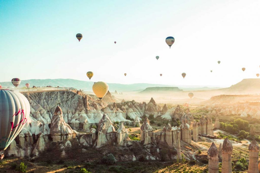 Travel photography image of hot air balloons in a canyon and mountains