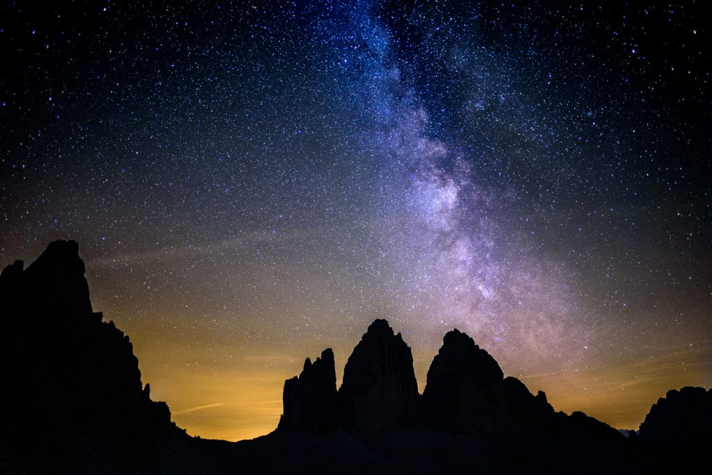 Astrophotography photo of the night ski behind desert mountains