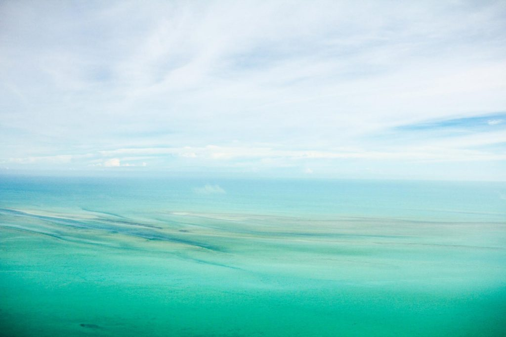 Fine art image of an ocean view with waves in water and blue sky with white clouds