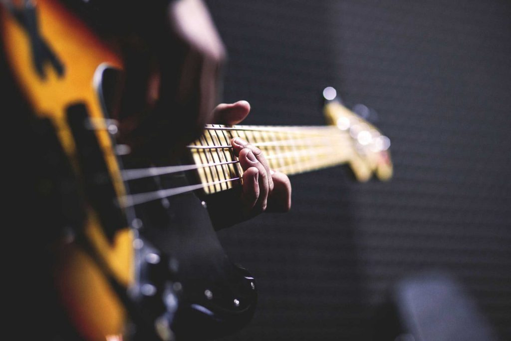 Up close image of someone playing an electric bass guitar