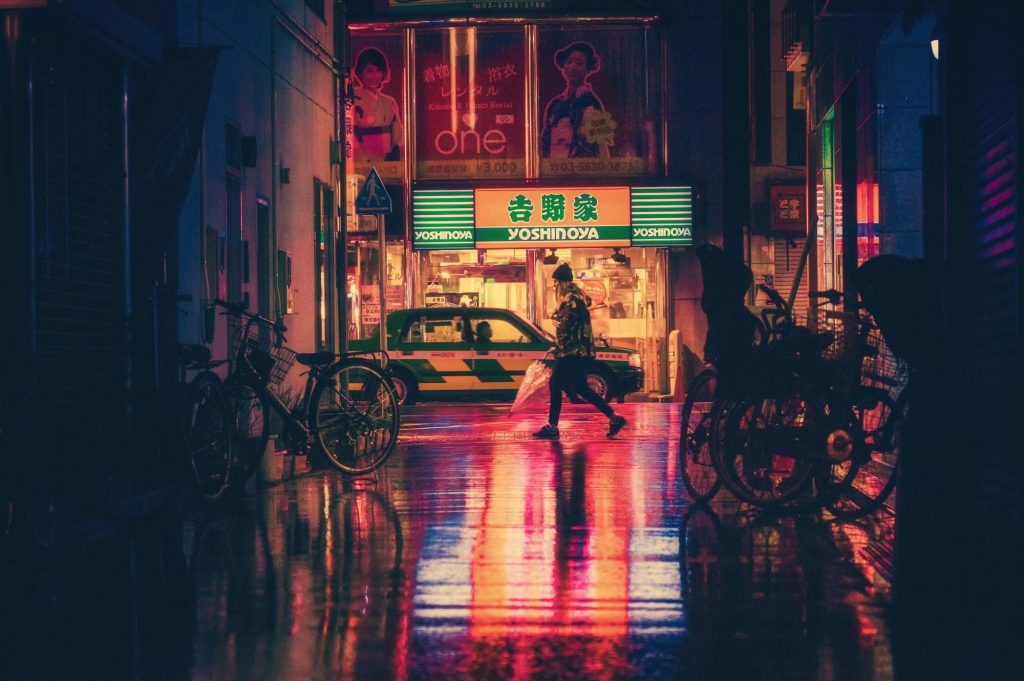 Urban photo of an alley with a woman with an umbrella walking in front of a store at night with a wet, reflective ground