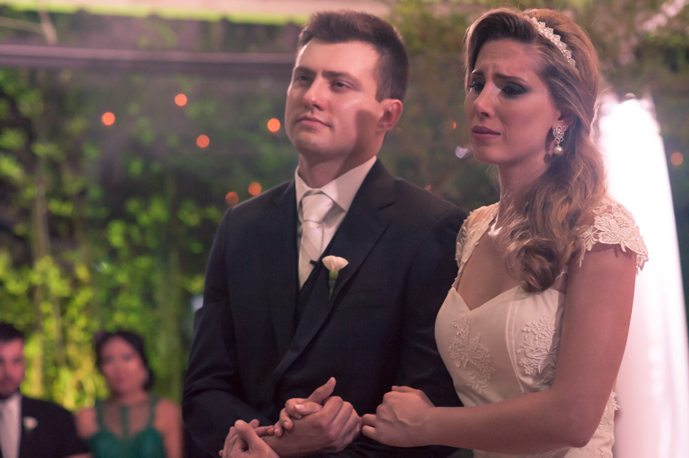 Wedding photography image of a bride and groom at the alter listening to their priest