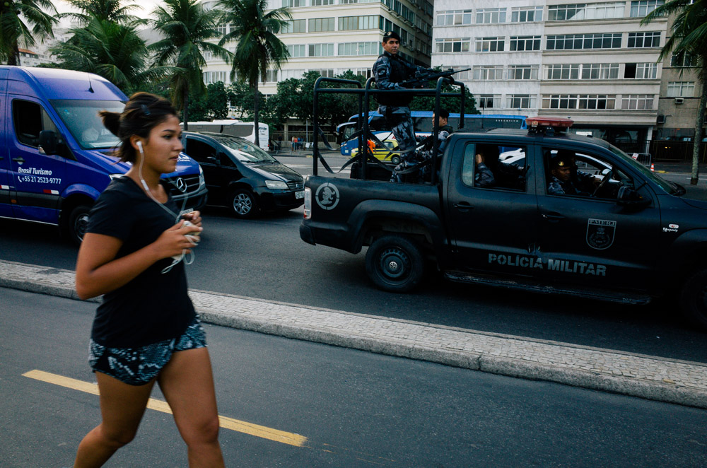 Street photography image of a woman running for exercise in Rio de Janeiro, Brazil, with a military vehicle behind her
