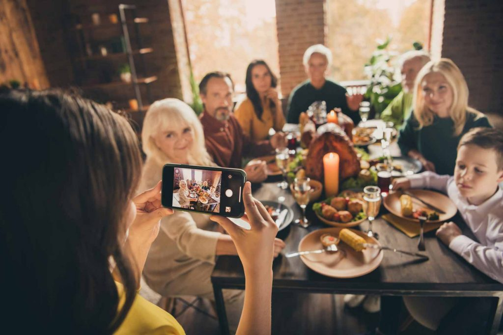 Image of a woman photographing a family at Thanksgiving dinner on her phone