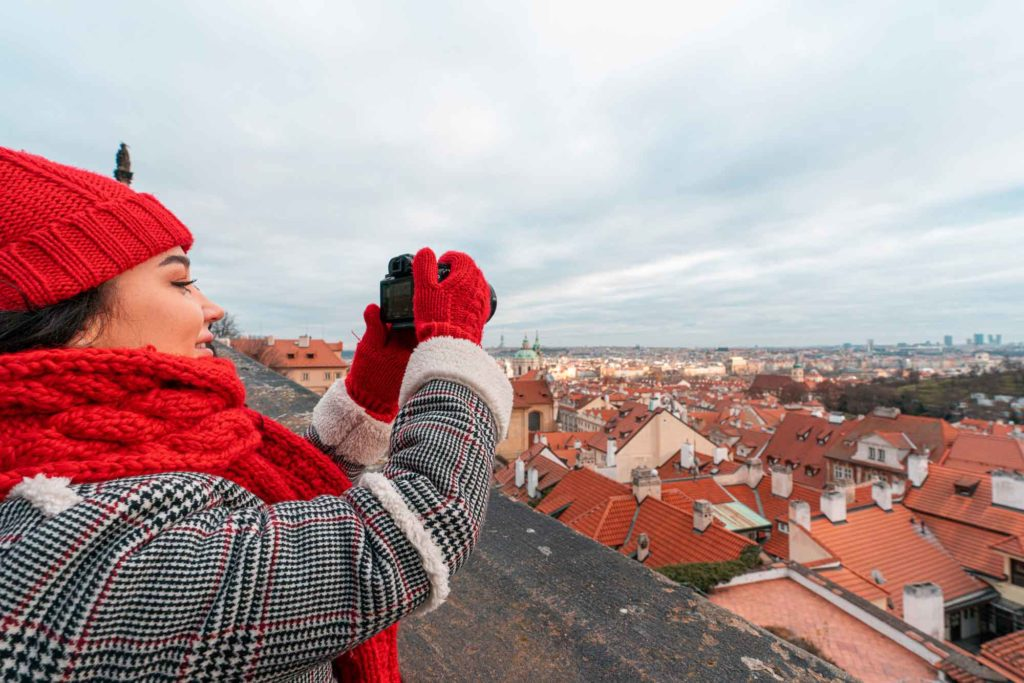 Image of a woman in a red scarf and hat taking Christmas images with a camera on a roof