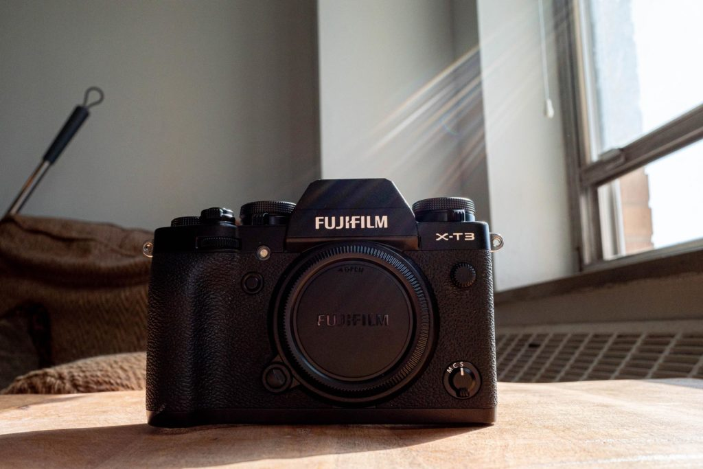 Image of the Fujifilm X-T3 on a wood table next to a window