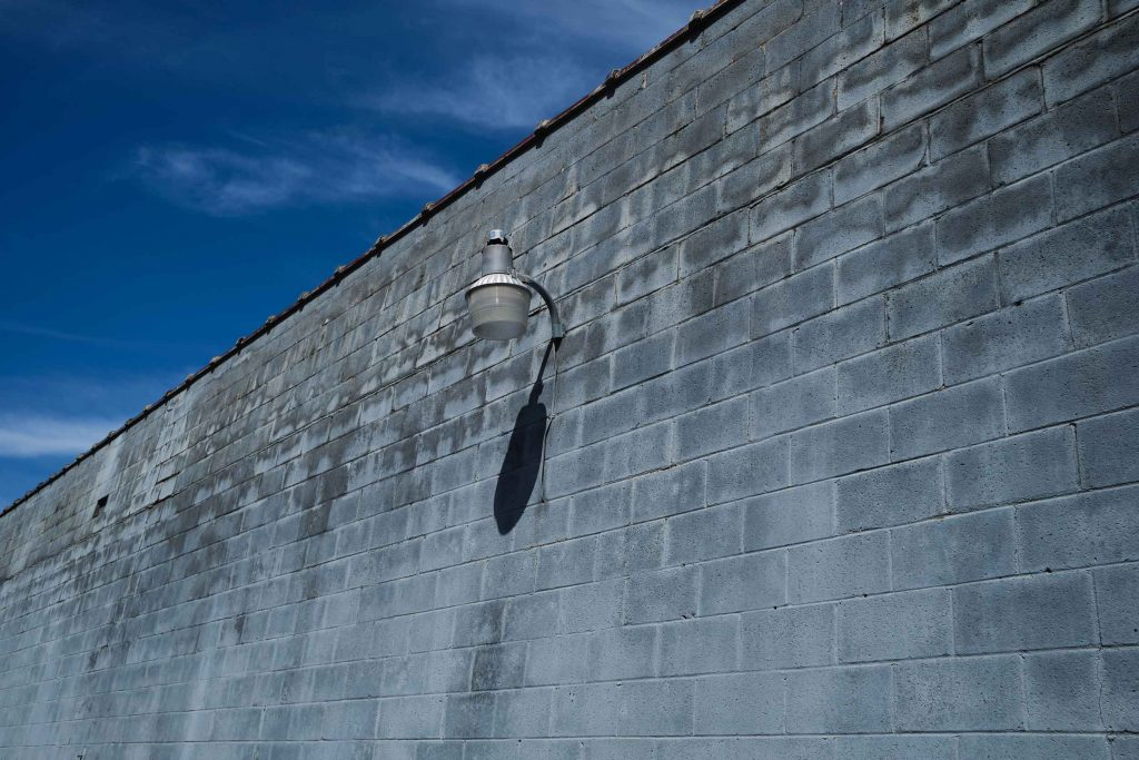 Urban landscape image of a gray wall and a street lamp shot with the Fujifilm X-E4 and the 23mm f/2